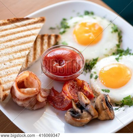Traditional American Continental Breakfast. Fried Eggs With Bacon, Mushrooms And Toast. Plate Of Pro