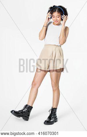 Woman jumping wearing headphones dancing to music