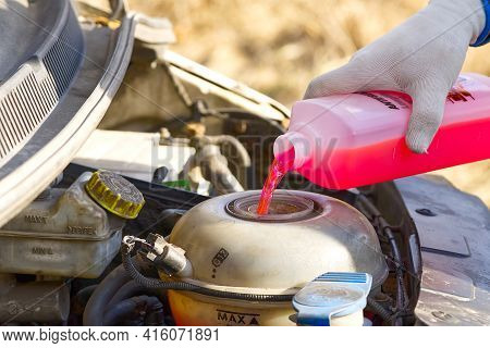 Pouring Coolant Service Of Cars. Pouring Antifreeze. Mechanic Fills The Coolant G12 To Tank In The E