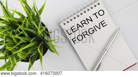 Keyword Learn To Forgive - Business Concept Text On White Notebook And Pen, Green Flowers