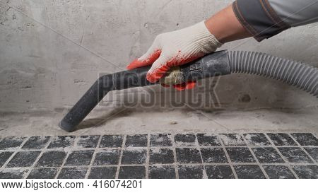 A Man Vacuums A Construction Site. Close-up Of A Cleaner In Special Clothing Holding A Brush From An