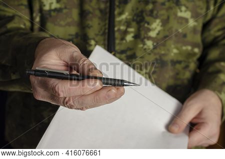An Officer Holds Out A Black Pen To The Camera. A Man's Hand Offers A Pen To Sign A Document. Adult