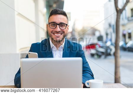 Businessman Looking To The Camera Using Laptop In A Cafe. Latino Businessman Smiling To The Camera O