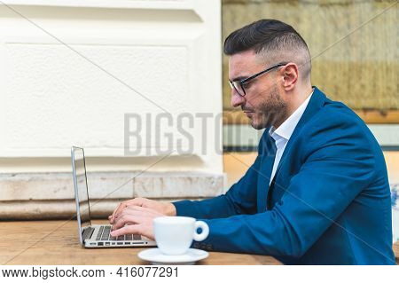 Businessman Using Laptop While Drinking Coffee In A Cafe. Latino Businessman Drinking Coffee While W
