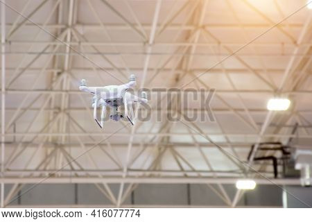 White Drone In Motion Flying From The Ceiling Inside The Building