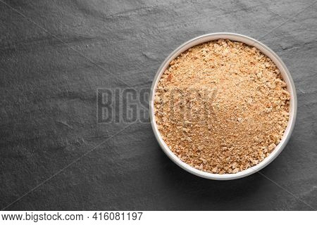 Fresh Breadcrumbs In Bowl On Black Table, Top View. Space For Text