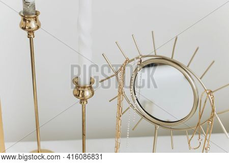 Modern Golden Boho Mirror With Gold Necklace And Vintage Candles  On White Table. Stylish Gold Acces