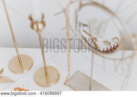 Modern Golden Accessories And Hair Clips Reflected In Boho Mirror On White Table With Vintage Candle