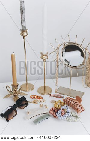 Modern Golden Jewellery, Hair Clips And Hairbands, Sunglasses On White Table With Vintage Candles An