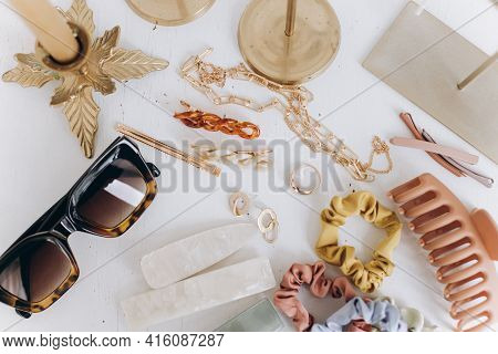 Modern Golden Jewellery, Hair Clips And Hairbands, Sunglasses On White Table With Vintage Candles. S