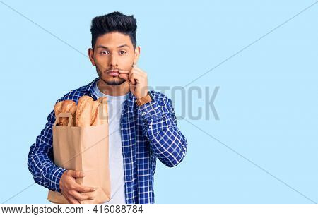Handsome latin american young man holding paper bag with bread mouth and lips shut as zip with fingers. secret and silent, taboo talking