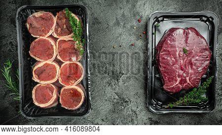 Raw Fresh Marbled Meat Steak Filet Mignon. Medallion Steaks Wrapped In Bacon On Dark Concrete Backgr