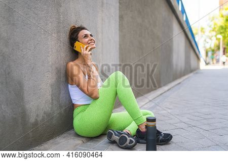Sporty Woman Having Phone Call After Exercising Outdoors.