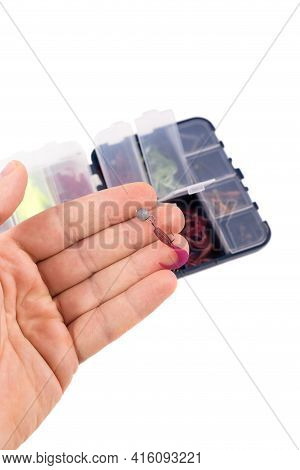 Male Hand Holds A Silicone Bait. Boxes With Silicone Baits In The Background. Studio Photo With Obje