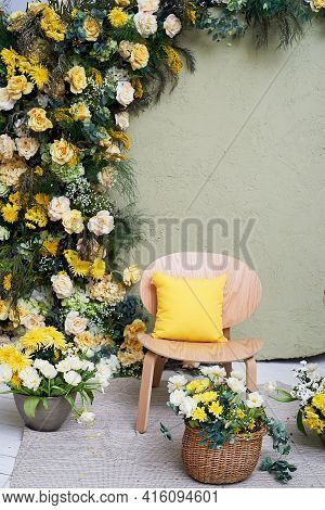 Spring Decoration Or Photo Zone. A Garland Of Flowers. Chair. Baskets With Yellow Flowers. Interior