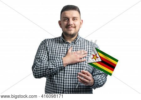 White Guy Holding A Flag Of Zimbabwe And Holds His Hand On His Heart Isolated On A White Background