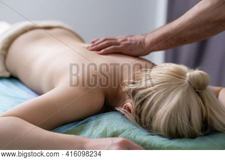 Massage And Body Care. Therapeutic Spa Body Massage. Woman Lying And Relaxing At Massage In A Cosy H