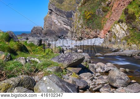 Rushing River Water Over Rocks And Boulders In A Scenic Countryside Valley