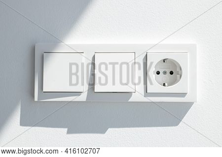 Modern White Switch Board With Two Switch And One European Plug. European Electrical Outlet