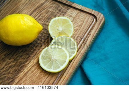 Slices Of Yellow Lemon And Whole Lemon On Wooden Cutting Board. Background Of Turquoise Fabric. Trop