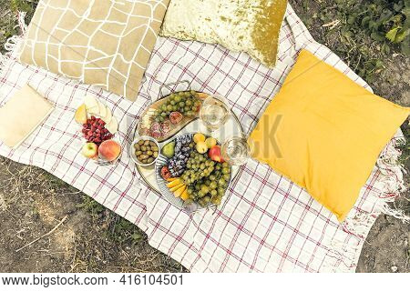 Pair Of Glasses With Wine Placed Near Tables With Various Fresh Ripe Fruits On Blanket With Cushions