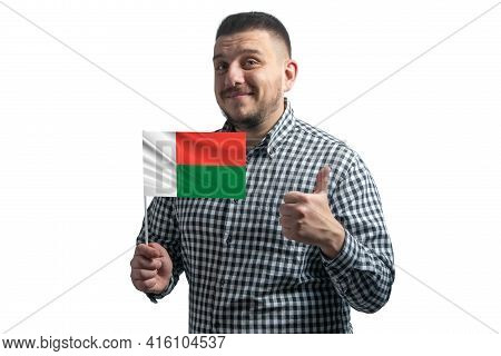 White Guy Holding A Flag Of Madagascar And Shows The Class By Hand Isolated On A White Background. L