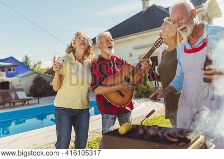Group Of Cheerful Senior Friends Having A Poolside Backyard Barbecue Party, Gathered Around The Gril
