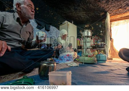 Mahan, Iran - 04.09.2019: Old Iranian Couple In Their Modest Cave Home, Preparing For Dinner. Mahan,