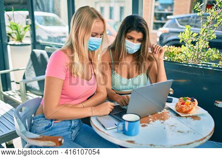 Two beautiful and young girl friends together using computer laptop at cafeteria wearing covid-19 safety mask