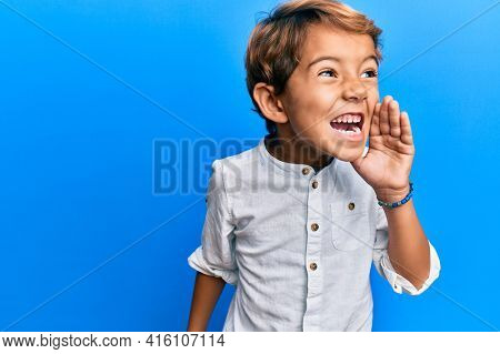 Adorable latin kid wearing casual clothes shouting and screaming loud to side with hand on mouth. communication concept.