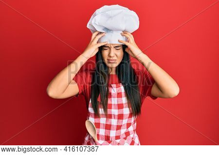 Young beautiful hispanic girl wearing baker uniform and cook hat suffering from headache desperate and stressed because pain and migraine. hands on head.