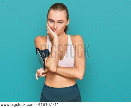 Beautiful young blonde woman wearing sportswear and arm band thinking looking tired and bored with depression problems with crossed arms.
