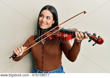 Young brunette woman playing violin smiling looking to the side and staring away thinking.