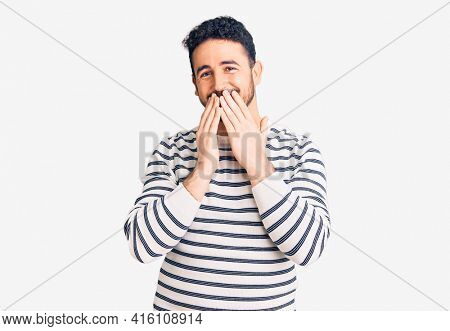 Young hispanic man wearing casual clothes laughing and embarrassed giggle covering mouth with hands, gossip and scandal concept