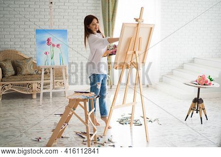 Cute Girl Artist Paints On Canvas Painting On The Easel. Model In The Studio.