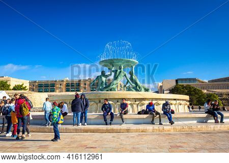 Valetta, Malta - January 11, 2019: People at the Iconic Triton fountain in front of the City Gate to Valletta, capital of Malta