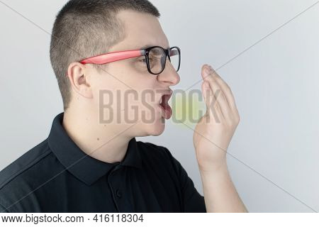 A Man With Bad Breath Looks At The Camera. Fetid Odor Concept. Close-up Of A Person Who Hears A Sten