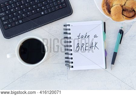 Take A Break. Concept Time Off. Words Take A Break In A Notebook On The Working Table With Cup Of Co