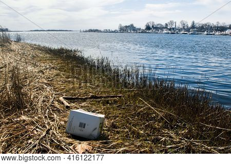 NORWALK, CT,USA  - APRIL 7, 2021: Empty paper box from beer Veterans Park near water in nice spring day