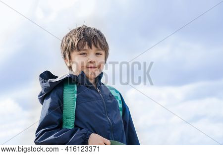 Kid With Dirty Mouth Of Chocolate Ice Cream With Blurry Sky Background,candid Shot Happy Child Stand