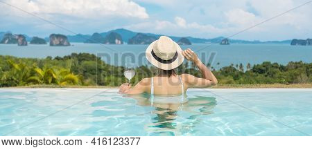 Happy Woman In White Swimsuit Drinking Wine In Luxury Swimming Pool Hotel Against Beautiful View, Yo