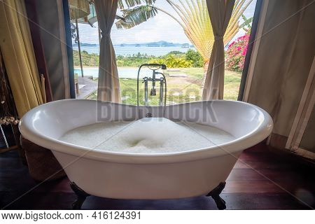Bathtub With Foam Bubbles In Tropical Luxury Resort Against Beautiful Ocean Background. Spa And Rela