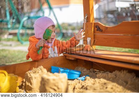Adorable Toddler Playing In The Sandbox. Cute Child In Fox Pajamas Plays In The Sand. Portrait Of A