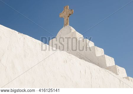 Close-up Of A White Roof Exterior Of A Church With A Stone Cross, Greece, Cyclades Islands, Mykonos.