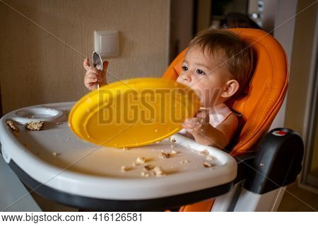 Adorable Baby Plays With  Plate At The Table. Little Child Indulges In A Baby Chair After Eating