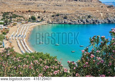 Sunbed Rows On Sandy Lindos Beach Near Turquoise Sea With Motorboats And People Swimming At Sunlight