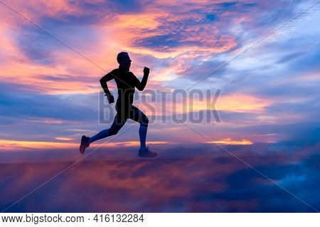 Running Athlete Silhouette On Fiery Clouds Background