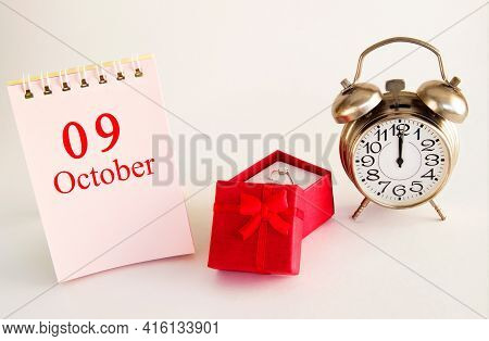 Calendar Date On Light Background With Red Gift Box With Ring And Alarm Clock With Copy Space. Octob