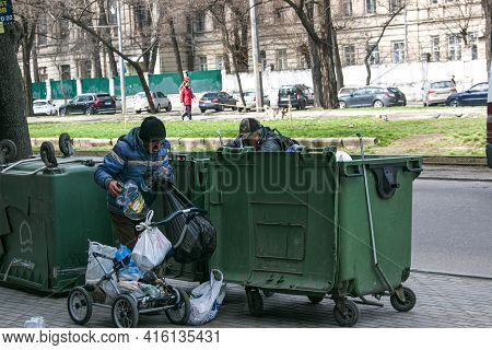 Dnepropetrovsk, Ukraine - 04.06.2021: Dirty Tramps Search For Food And Used Pet Bottles In A Trash B