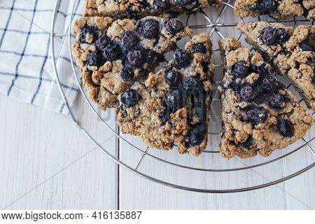 Freshly Baked Oat Blueberry Scones On Cooling Rack On White Wooden Background. Vegan And Plant Based